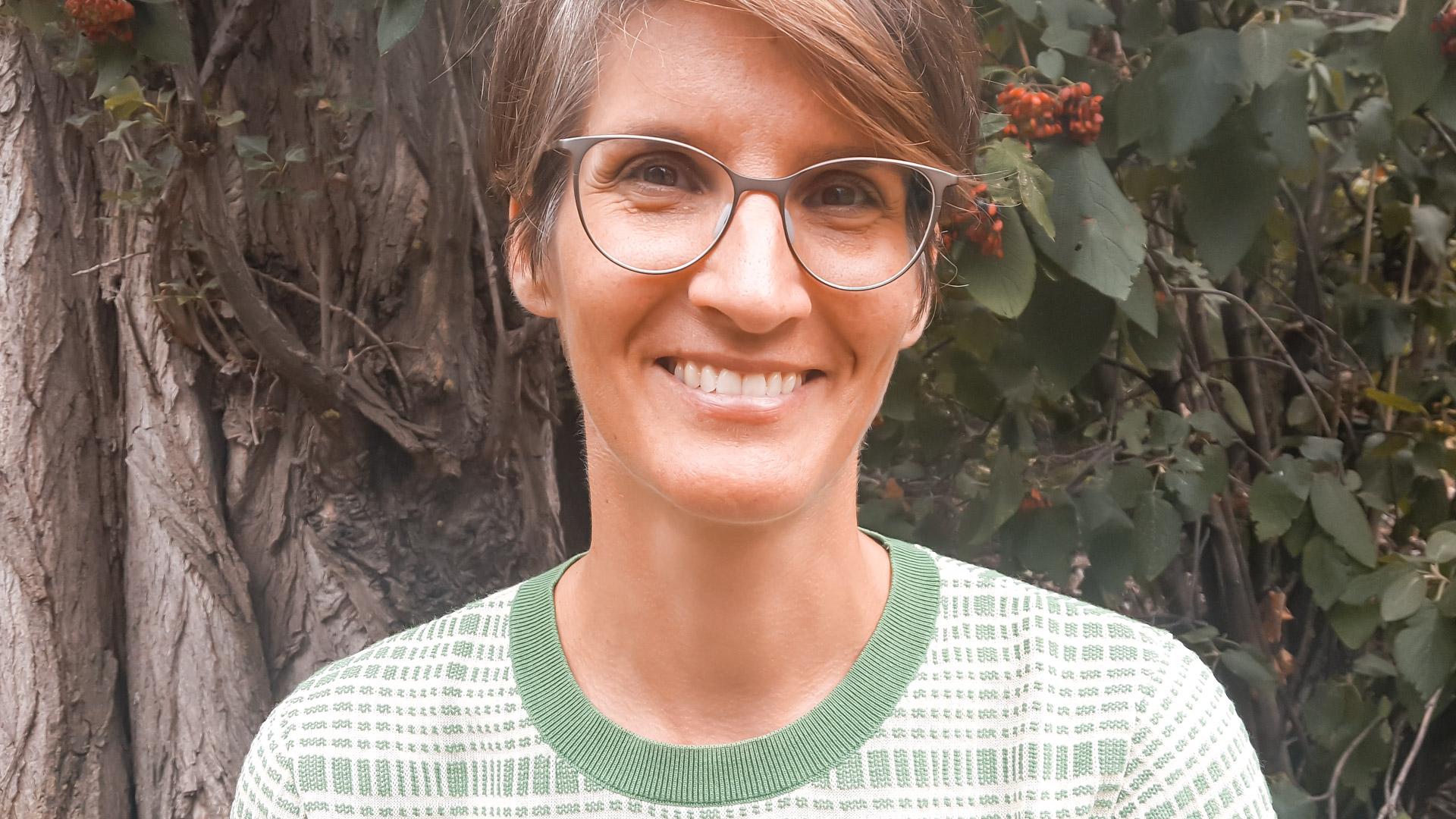 Martina Jauschneg lächelnd vor einem Baum